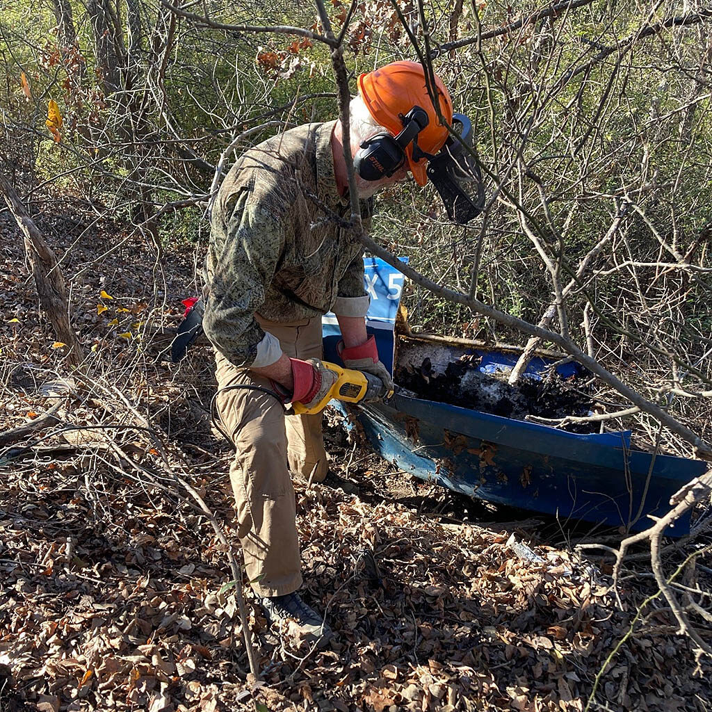 Friends member Bert Slade using a saw to cut up an old boat at the Fort Worth Nature Center