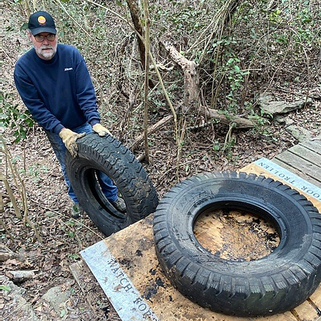 Friends member Jaime Dickerson rolling old tires down the creek at the Fort Worth Nature Center