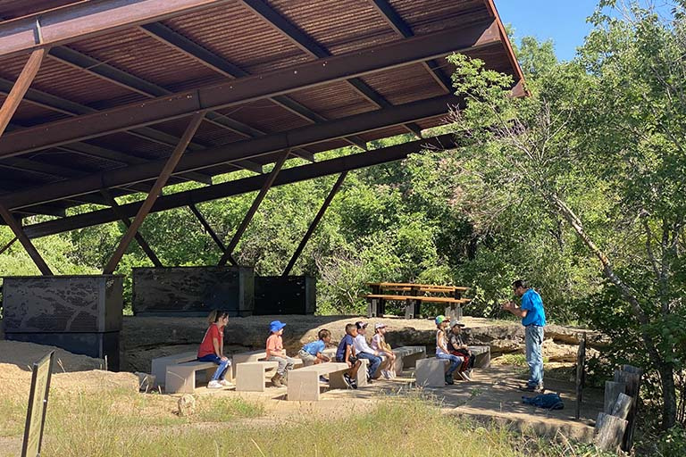 Michael Perez teaching young campers about nature under the cover of the Lotus Marsh Pavilion at the Fort Worth Nature Center