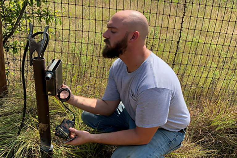 Staff member installing a trail counter box for the Trail Counter Project at the Fort Worth Nature Center