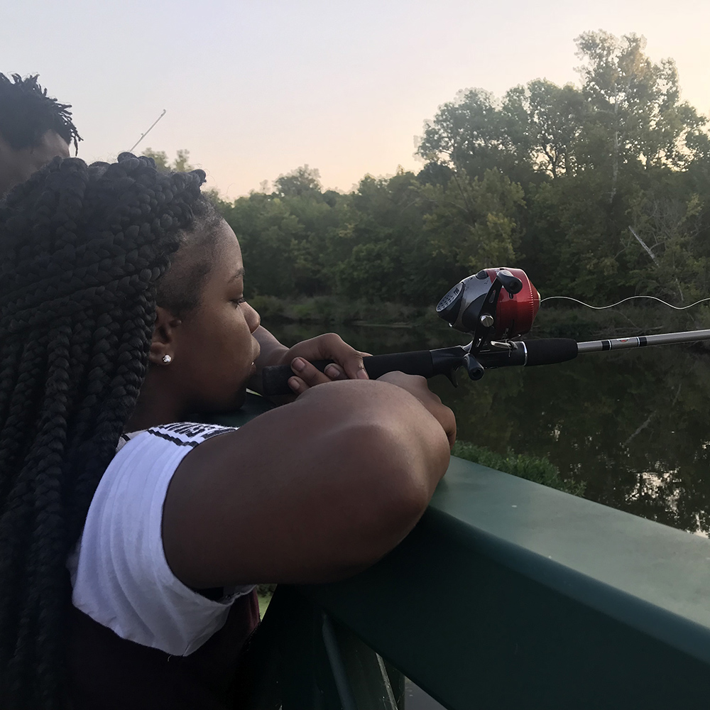 Teenage girl fishing from a bridge at the Fort Worth Nature Center