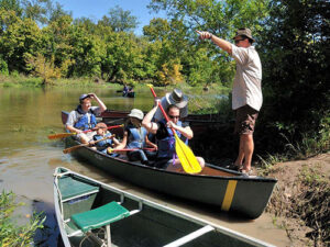 Volunteer helping to launch a canoe at the Fort Worth Nature Center