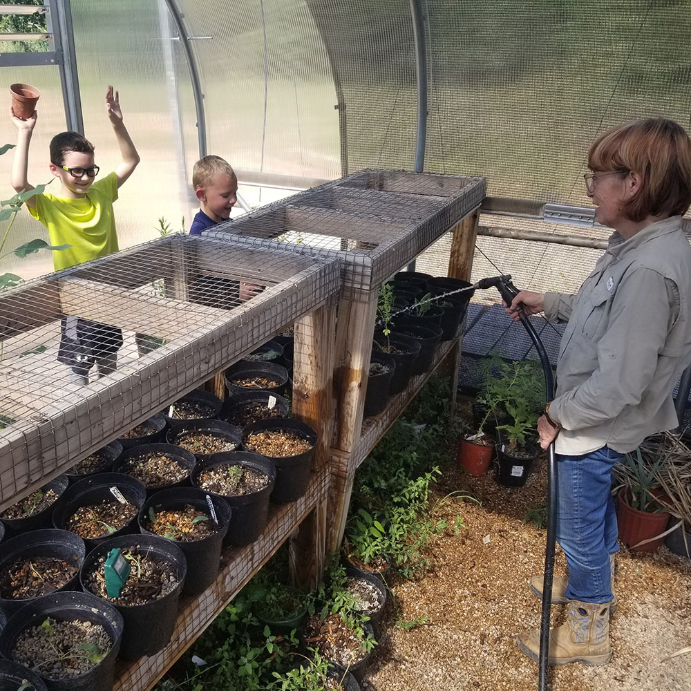 Young campers helping at the greenhouse during Summer Natural History Adventure at the Fort Worth Nature Center
