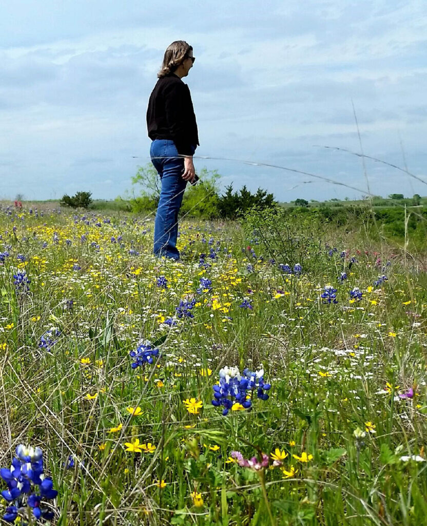 Suzanne Tuttle in a field of flowers gazing out over the prairie at the Fort Worth Nature Center