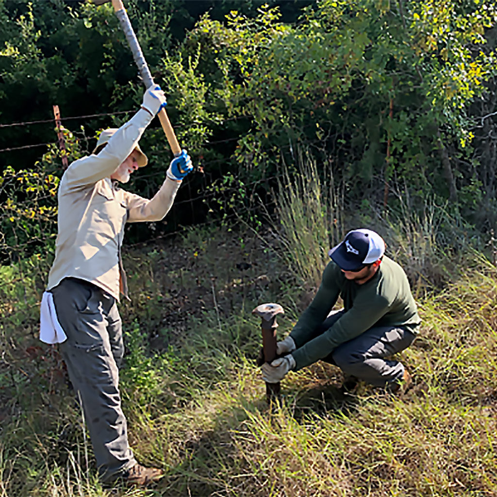 Staff installing a post to mount a trail counter at the Fort Worth Nature Center