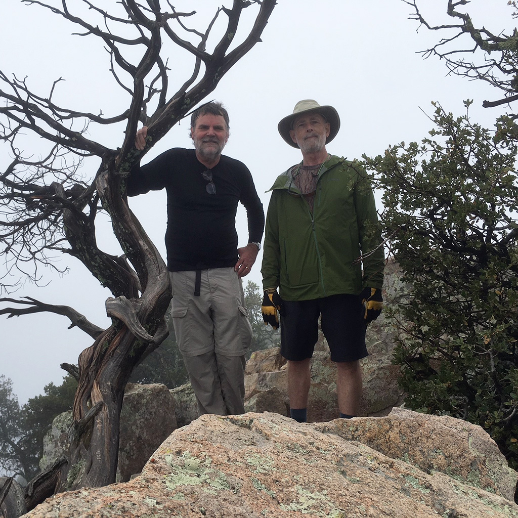 Friends members Jaime Dickerson and Bert Slade standing on a rock formation next to a gnarled tree at Big Bend National Park