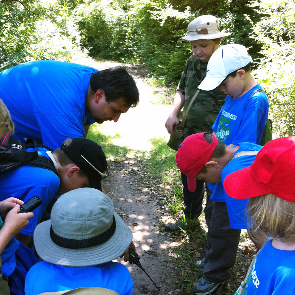 Staff naturalist showing kids wildlife tracks on a trail at the Fort Worth Nature Center